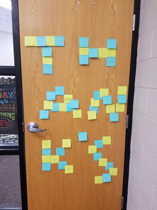 "A classroom door with ""Thanks' written in post-it notes"