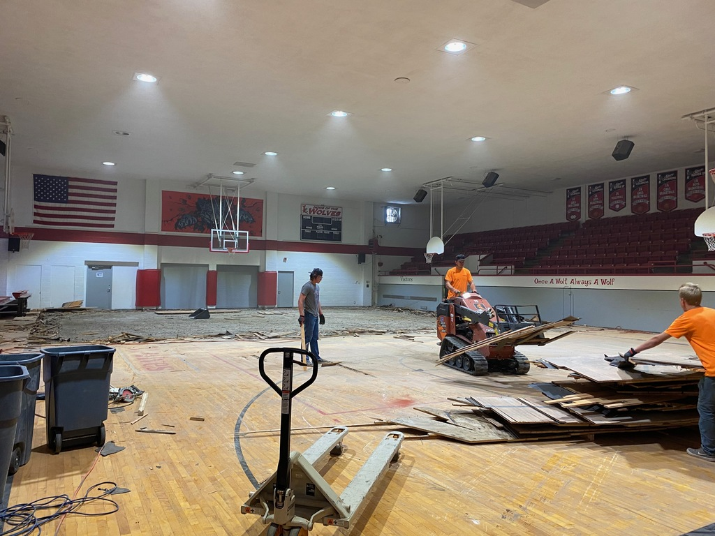 workers taking out gym floor